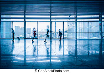 commuters motion blurred in modern corridor - commuters...