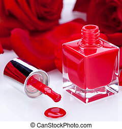 Elegant red nail varnish in a stylish bottle surrounded by...