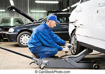 auto mechanic at repair work - mechanic matching automobile...