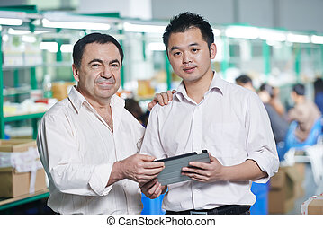 manager and chinese worker in factory - caucasian...