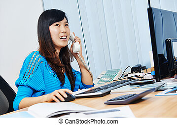 chinese office manager woman speaking on phone at work place