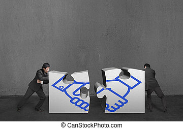 Businessmen push two heavy puzzles together with shake hand...