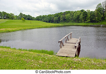 wooden pier on lake in summer