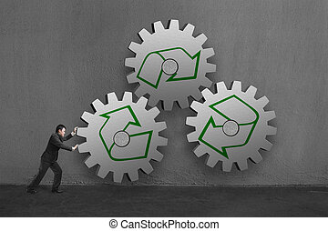 Businessman rolling 3 large concrete gears with recycle mark in concrete wall background.