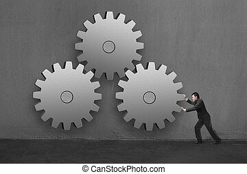 Businessman rolling 3 large concrete gears in concrete wall background.