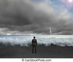 Businessman standing toward waves and cludy sky with...