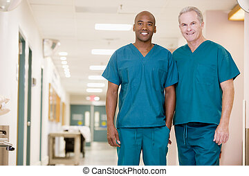 Two Orderlies Standing In A Hospital Corridor