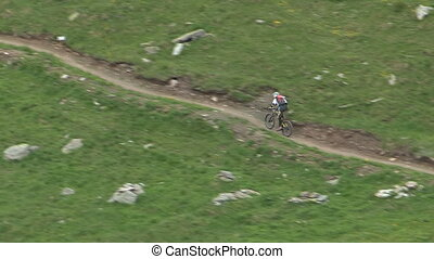 Cyclist going downhill on countryside path
