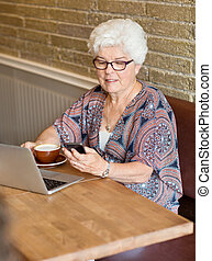 Woman Text Messaging Through Smartphone In Cafe - Senior...