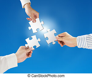 Team work concept, Hands hold puzzles with clear blue sky...