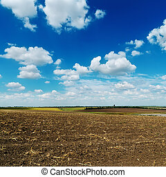 blue cloudy sky over plowed field