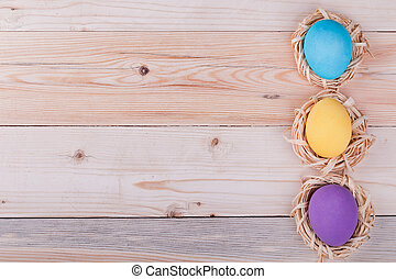 Three Easter eggs in small nests on wooden background, top...