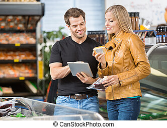 Couple Using Digital Tablet At Butcher's Shop - Couple using...