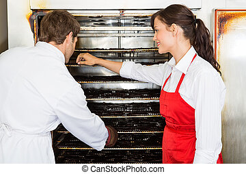 Workers Drying Meat In Oven At Butchers Shop - Male and...