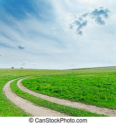 dirty road in green grass under cloudy sky