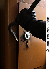 Burglar breaking the safe - Burglar in black gloves breaking...