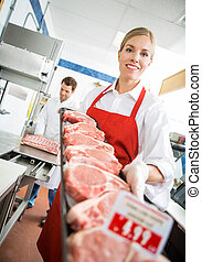 Happy Butcher Showing Meat Tray In Store - Portrait of happy...