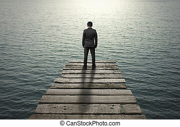 Businessman standing and thinking on old wooden pier to the...