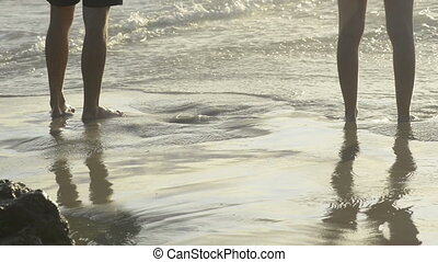 Feet In Water - Couple stand with bare feet in the water at...