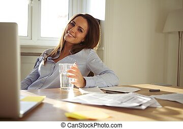 Woman working in home office smiling at camera - Pretty...