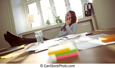 Beautiful business woman talking on cell phone - Smiling and...