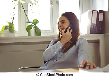 Pretty woman talking on mobile phone in home office - Pretty...