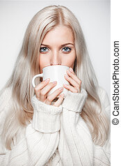 Blonde woman drinking a cap of tea - Blonde young woman...