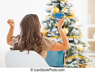 Young woman with credit card and laptop rejoicing success...