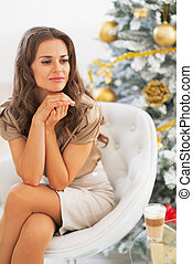 Portrait of young woman sitting near christmas tree