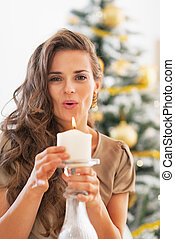 Young woman blowing candle in front of christmas tree