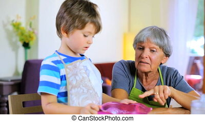 Boy teaching grandma how to cook - Grandmother talking happy...