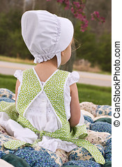 Amish Child sitting on an old biscuit quilt