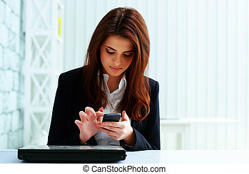 Young serious businesswoman typing on her smartphone in...