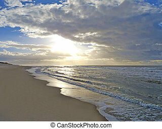 sunset at the beach - moody sunsetand cloudy sky at a...