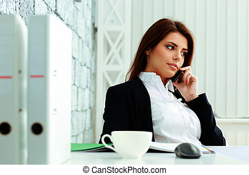 Young beautiful businesswoman talking on the phone at office