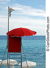 Red  lifeguard tower with white flag over clear blue sky