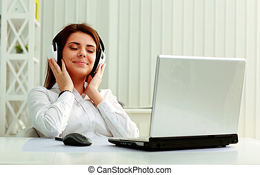 Young beautiful businesswoman listening music in headphones...