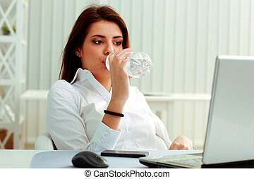 Young businesswoman drinks water on her workplace in office
