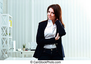 Young happy businesswoman leaning at the table in office