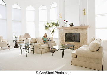 Woman reading magazine in living room