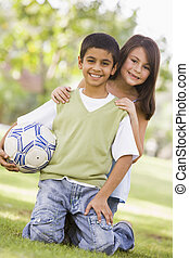 Two young children outdoors in park with ball smiling (selective focus)