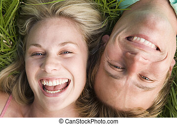 Couple lying in grass smiling