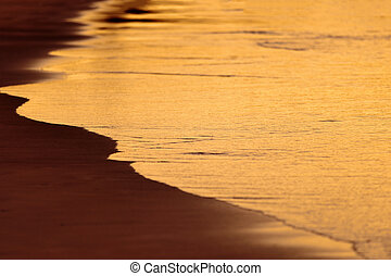 Afterglow - Smooth wave on the sandy beach in the evening
