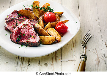 Roast beef steak with potato wedges and tomato - Succulent...