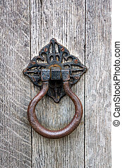 Old door knocker on a weathered oak door