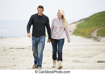 Couple walking at beach holding hands smiling