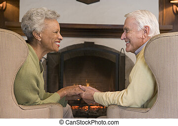 Couple sitting in living room by fireplace holding hands and...