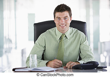 Businessman sitting in office with personal organizer...