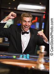 Man in casino winning at roulette and smiling (selective focus)