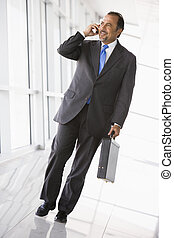 Businessman walking in corridor on cellular phone smiling...